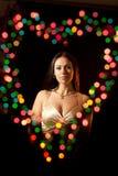 Mulher em um halo sob a forma do coração Imagens de Stock