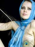 Mulher em um lenço e com uma pena Fotografia de Stock Royalty Free