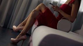 Mulher em um noivo de espera do vestido vermelho impressionante para pegará-la por uma data foto de stock