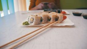Mulher em um restaurante japonês e placas do sushi Rolls em uma tabela de madeira à moda branca Tiro da zorra filme