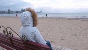 Mulher em um revestimento branco da pena que senta-se em um banco na praia e no olhar na distância inverno do mar, vista traseira vídeos de arquivo