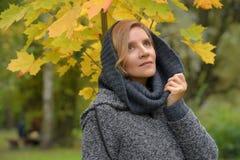 Mulher em um revestimento cinzento com uma capa imagens de stock royalty free