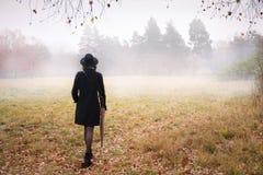 Mulher em um revestimento no tempo nevoento fotografia de stock
