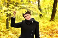 Mulher em um revestimento preto sob um ramo do bordo do outono fotografia de stock royalty free