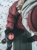 Mulher em um revestimento vermelho do inverno, em um lenço cinzento e em umas luvas pretas em guardar um copo do chá com suas mão Imagens de Stock Royalty Free