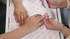Mulher em um salão de beleza do prego que recebe o tratamento de mãos pelo esteticista Fotos de Stock Royalty Free