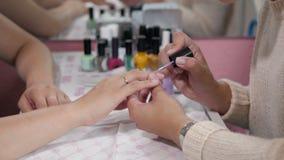 Mulher em um salão de beleza do prego que recebe o tratamento de mãos pelo esteticista Imagem de Stock