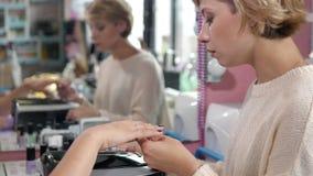 Mulher em um salão de beleza do prego que recebe o tratamento de mãos pelo esteticista com arquivo começar pregos ao cliente borr Imagens de Stock