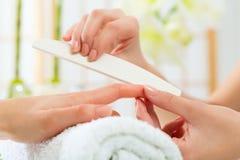 Mulher no salão de beleza do prego que recebe o manicure Imagem de Stock