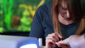 Mulher em um salão de beleza que recebe um tratamento de mãos vídeos de arquivo