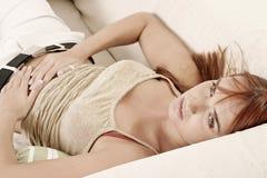 Mulher em um sofá Imagens de Stock Royalty Free