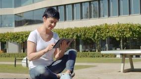 Mulher em um t-shirt branco que senta-se na frente de um prédio de escritórios e que trabalha em uma tabuleta vídeos de arquivo