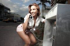 Mulher em um telefone de pagamento imagem de stock