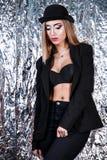 Mulher em um terno do preto do vintage no fundo da folha de alumínio fotos de stock royalty free