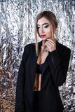 Mulher em um terno do preto do vintage no fundo da folha de alumínio imagem de stock