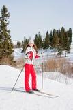 Mulher em um terno ostentando no in-field dos esquis Fotografia de Stock Royalty Free