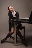 Mulher em um terno preto que senta-se em uma tabela do escritório Imagem de Stock