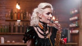 A mulher em um traje de couro escuro executa uma música em um saxofone video estoque