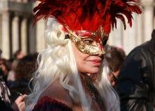 Mulher em um traje e máscara com as penas vermelhas no carnaval em Veneza, Itália Fotos de Stock