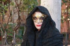Mulher em um traje preto e em uma máscara dourada que levantam no carnaval de Veneza em Itália Foto de Stock