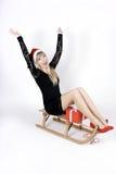 Mulher em um trenó com presente Imagem de Stock Royalty Free
