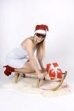Mulher em um trenó com presente Imagens de Stock Royalty Free