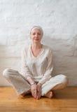 Mulher em um turbante que senta-se em um assoalho de madeira perto da parede Fotos de Stock Royalty Free