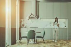 A mulher em um verde preside a sala de jantar e a cozinha Imagem de Stock Royalty Free