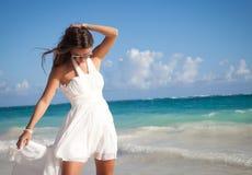 Mulher em um vestido branco na costa do oceano Imagens de Stock Royalty Free
