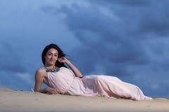 Mulher em um vestido branco que encontra-se em uma duna de areia Imagens de Stock