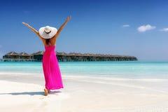 A mulher em um vestido cor-de-rosa do verão está em uma praia tropical em Maldivas foto de stock