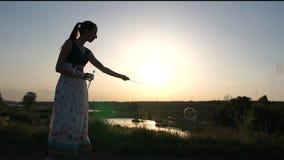 A mulher em um vestido faz bolhas de sabão no por do sol no movimento lento vídeos de arquivo
