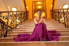 Mulher em um vestido longo nas escadas Imagens de Stock Royalty Free