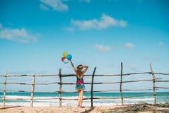 A mulher em um vestido olha o oceano As posses balloons à disposição horizonte imagem de stock