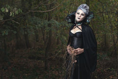 Mulher em um vestido preto na floresta imagem de stock