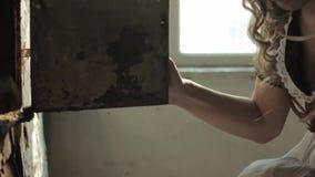 Mulher em um vestido rústico que senta-se ao lado do fogão velho em uma casa abandonada arruinada vídeos de arquivo