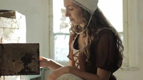 Mulher em um vestido rústico que senta-se ao lado do fogão velho em uma casa abandonada arruinada filme