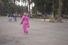 A mulher em um vestido roxo que dê uma volta em torno do quadrado após a compra o mercado imagem de stock royalty free