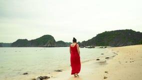 A mulher em um vestido vermelho anda na costa da ilha Vista traseira Ressaca do oceano Console tropical Traços de pés sobre vídeos de arquivo