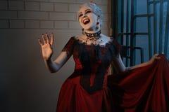Mulher em um vestido vermelho com sorrir forçadamente do vampiro fotografia de stock royalty free
