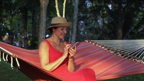 A mulher em um vestido vermelho senta-se em uma rede vermelha em um jardim tropical Solar na ilha de Phu Quoc A mulher senta-se n vídeos de arquivo