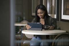 Mulher em uma cafetaria com uma tabuleta foto de stock royalty free