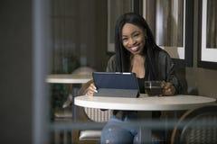 Mulher em uma cafetaria com uma tabuleta fotografia de stock