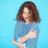 Mulher em uma camisa listrada com os olhos fechados no fundo azul Imagem de Stock