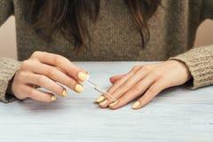 Mulher em uma camiseta marrom com o tratamento de mãos amarelo que aplica o cosmético foto de stock royalty free