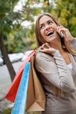 Mulher em uma chamada ao levar sacos de compras Imagens de Stock Royalty Free