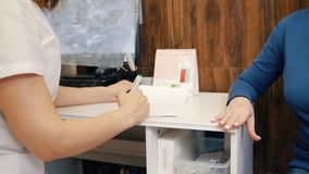 Mulher em uma clínica da cosmetologia Consulta com um especialista sobre pregos filme