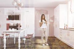 Mulher em uma cozinha luxuosa com uma tabela de mármore Imagens de Stock Royalty Free