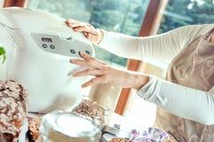 A mulher em uma cozinha moderna ajusta uma máquina para cozer Fotografia de Stock Royalty Free
