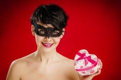 Mulher em uma máscara com um presente Foto de Stock Royalty Free